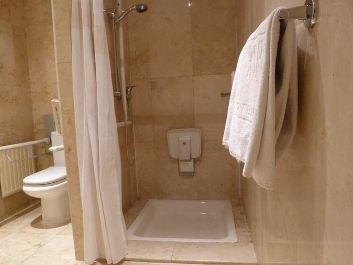 Al otro lado de la ducha hay un asiento que es inalcanzable tanto cuando está plegado como cuando está desplegado.