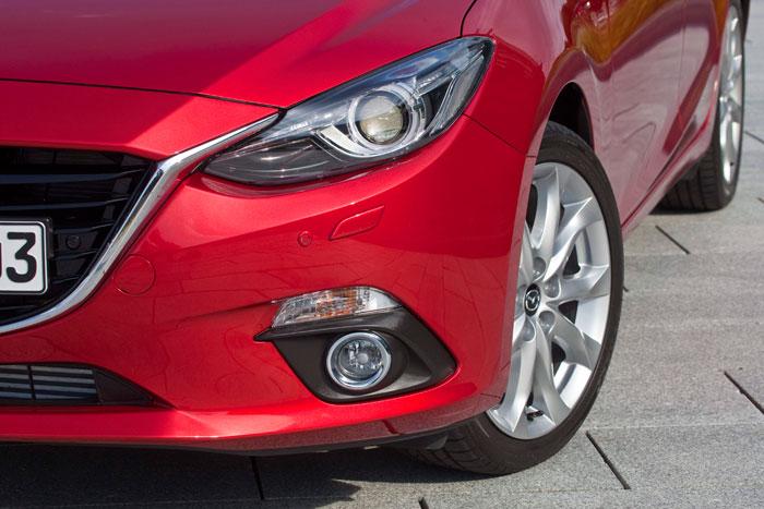 """Hasta el momento, todos los Mazda-3 que hemos probado llevaban la llanta de 18"""" que aparece en la foto, así como el faro de xenón, fijo o móvil, según los casos."""