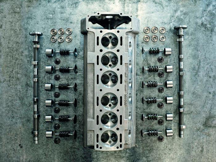 La clave del motor XK: la culata de doble árbol aparecida en 1948, que situó a Jaguar en cabeza del mercado al ofrecer dicha tecnología a unos precios bastante asequibles (berlina Mk.VII y deportivo XK-120). En principio el ángulo entre válvulas era de 70º; pero la de alto rendimiento (o sea ésta) lo abrió hasta 80º para poner válvulas más grandes. Quizás el tamaño de la foto no permita apreciar el doble muelle interior de hélice invertida, con el antivibrador elástico interpuesto entre ambos.