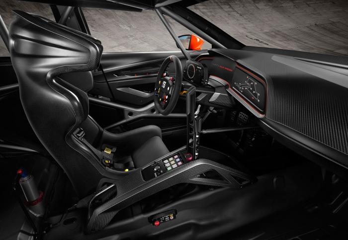 """Puesto de pilotaje del CupRacer: con semejante asiento, más el HANS, el piloto nunca debería """"perder la cabeza"""". El cambio secuencial se maneja manual y directamente mediante una robusta bieleta de aluminio. A la derecha de la consola se dispone del plano del circuito, con la posición del coche, por si """"se pierde la cabeza"""". En la pantalla frontal, la línea roja está en 6.000 rpm; menos de las 6.500 del Cupra de serie, ya que el cambio más cerrado y el mayor par a medio régimen así lo aconsejan. También aparece la marcha en la que se va, el tiempo en la vuelta anterior y, en digital, la velocidad y la temperatura del agua."""