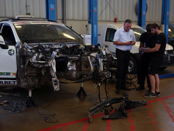 En el taller del importador VW en Dar-es-Salam, revisando los daños: el larguero inferior derecho, los dos superiores y la torreta de suspensión derecha, hechos papilla. Pero cumplieron su función amortiguadora de otros daños.