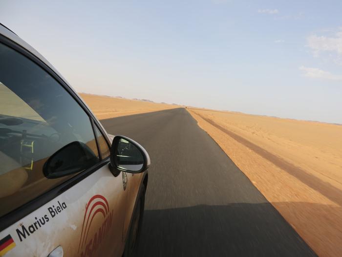 """Curiosidades de las carreteras: gran recta entre Egipto y Sudán, en mitad del desierto: el asfalto es perfecto, aunque sin líneas pintadas; claro que para el tráfico que parece que hay, tampoco hacen mucha falta. Eso sí, se nota que un """"angledozer"""" pasa con frecuencia, limpiando la arena y formando con ella una pequeña barrera protectora."""