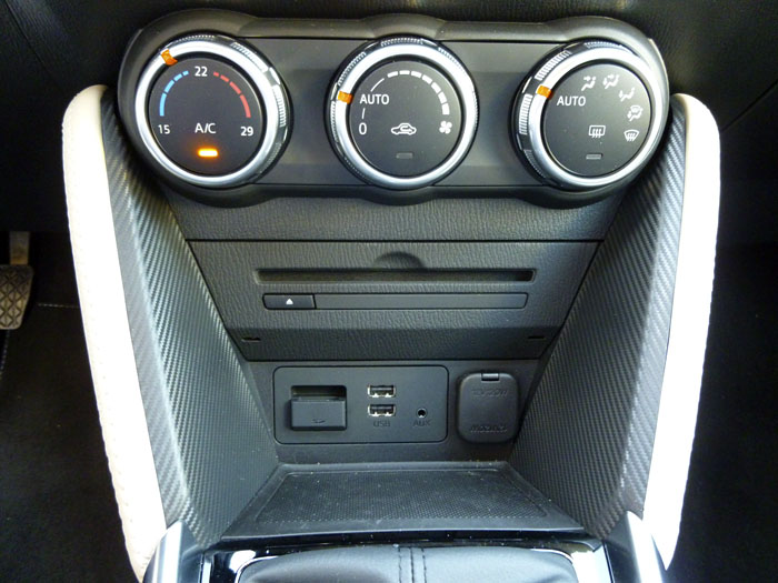 Mazda2 2015. Mandos del climatizador, toma de corriente, cargador CD, USB...