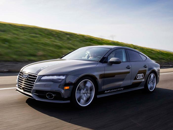 El imponente Audi A7 Sportback 3.0-TFSI quattro S-tronic en pleno recorrido (de madrugada o al atardecer, a juzgar por la sombra).