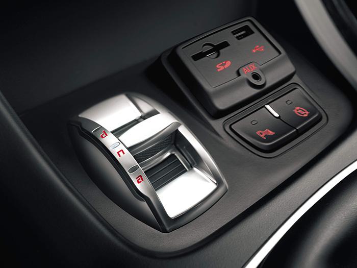 """En la consola central, por delante de la palanca de cambios, el selector """"biológico"""" (ADN) de modos de conducción, así como los enchufes para conexiones, y los interruptores del Stop/Start y del parking."""