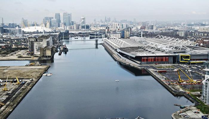 En la dársena de Canary Wharf (London Business District) el Jaguar XF aparece como un diminuto punto blanco colgado sobre el agua, a mitad de su recorrido. A uno y otro lado, las grúas que sujetan el conjunto de cables.