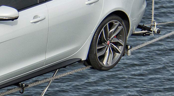 """No parece probable que el XF pueda salirse de los cables: tanto delante como detrás lleva dobles rodillos verticales para el guiaje lateral, y hay seis abrazaderas (cuatro junto a los rodillos y dos a mitad del coche en una barra transversal visible en la foto anterior) que impiden que los cables se separen en vertical de la carrocería. En cuanto a los neumáticos, están cortados en el centro de la banda de rodaje, dejando los hombros para dar una imagen """"normal"""" y colaborar al guiado lateral, si es que hiciese falta (para eso están los rodillos)."""