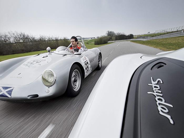 Mark Webber pilota un 550A (no muy en serio, va sin casco) siguiendo a un Boxster Spyder actual, en las pistas de pruebas que Porsche tiene junto al circuito británico de Silverstone. A pesar de la cruz escocesa, la unidad pertenece actualmente al taller del ex-piloto americano Bob Estes de Beverly Hills (California), como puede leerse (aumentando la foto) en la portezuela.