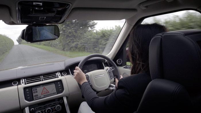 """El Range-Rover de nuestra amazona lleva instalados los dos sistemas comentados en esta entrada; y mientras por el espejo central puede controlar la carretera mediante el Transparent Trailer (el chasis del remolque aparece muy difuminado en la zona inferior), en la pantalla del salpicadero, al tener seleccionada la función """"Cargo Status"""", el Cargo Sense le advierte, mediante un zumbador y un triángulo rojo, que hay una incidencia en el interior del remolque. Un toque al mando adecuado, y la imagen pasa a ser la de dicho interior, para controlar qué le ocurre al caballo."""