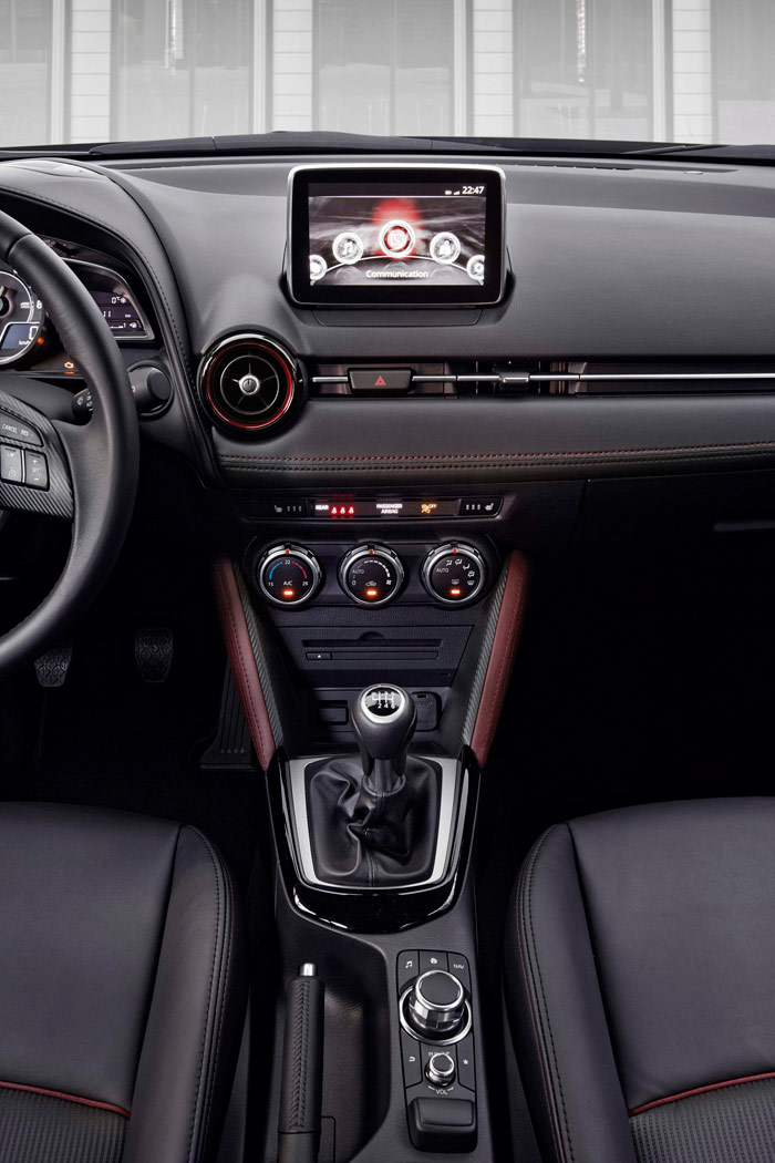 Las consolas están alineadas sobre un eje central, desde la pantalla arriba del todo, pasando por los mandos de climatización, la palanca de cambios y los botones de audio e infotainment.