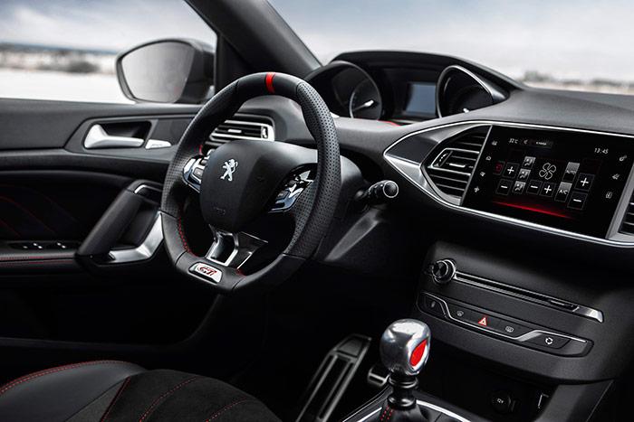 El puesto de conducción apenas si difiere del de un 308 de acabado alto pero mecánica tranquila, a no ser por la señal de posición superior en el volante.
