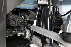 Detalle de la barra de la dirección, barra estabilizadora (en la parte inferior), brazo inferior  en sentido  transversal a la marcha y parte del conjunto muelle-amortiguador.