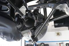 Detalle de la parte posterior del buje trasero. Se aprecia con claridad el anclaje de todos los brazos de la suspensión, de la barra estabilizadora y el árbol de transmisión.