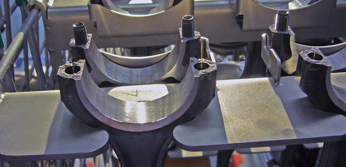 Las bielas se cortan por fractura en frío. Este sistema deja una superficie irregular que no quedaría en un corte limpio. Precisamente eso es lo que se busca. Las irregularidades permiten volver a juntar con precisión las dos mitades.