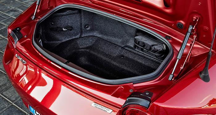 El pequeño maletero de 130 litros (totales, con hueco inferior incluido) tiene una forma bastante aprovechable, para dos maletas de tamaño cabina de avión, o poco más. Sujeto con una banda y en una bolsa con cremallera, va el kit antipinchazos.