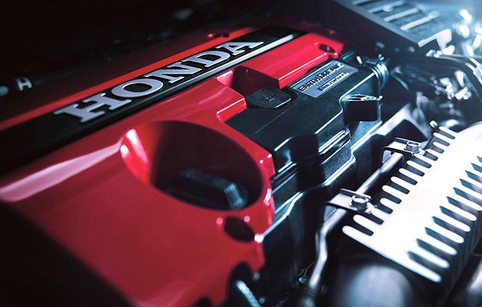 """Típico de los motores Honda de alto rendimiento: el culatín se presenta acabado en rojo; en modelos anteriores incluso la superficie era de aspecto """"craquelé"""" rugoso, como en los Ferrari. En cuanto al colector de admisión de aluminio lleva un vistoso aleteado que contribuye a rebajar la temperatura del aire de admisión (no mezcla, al ser de inyección directa)."""