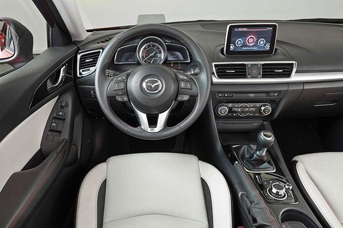 El puesto de conducción de los Mazda es, dentro de la complicación de casi cualquier coche actual, de los más racionales y ergonómicos. Los mandos están bastante repartidos entre consolas, volante (botones muy pequeños, pero no tiene remedio) y puerta. Y el mando giratorio y pulsante situado tras de la palanca de cambios resulta bastante fácil de comprender y manejar.